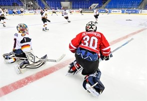 SOCHI, RUSSIA - APRIL 20: Germany's Kevin Reich #1 and Canada's Philippe Desrosiers #30 stretch in the neutral zone in warm-up during preliminary round action at the 2013 IIHF Ice Hockey U18 World Championship. (Photo by Matthew Murnaghan/HHOF-IIHF Images)