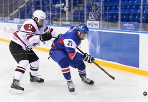 SOCHI, RUSSIA - APRIL 26: Latvia's Janis Jaks #21 and Slovakia's David Soltes #21 battle for the puck near the boards during relegation round action 2013 IIHF Ice Hockey U18 World Championship. (Photo by Matthew Murnaghan/HHOF-IIHF Images)